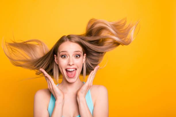 귀여운 스트레이트 머리 금발 백인 웃는 소녀, 놀된, 캐주얼 블루 셔츠를 입고 흥분, 보여주는 바람 불면 머리. 노란색 배경 위에 절연 - 장엄한 뉴스 사진 이미지