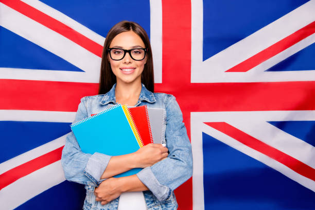 Portrait of cute sweet lovely confident smiling student lady emi Portrait of cute sweet lovely confident smiling student lady emigrant wearing spectacles, casual denim jeans, holding notepads, isolated over Great Britain union jack flag english language stock pictures, royalty-free photos & images