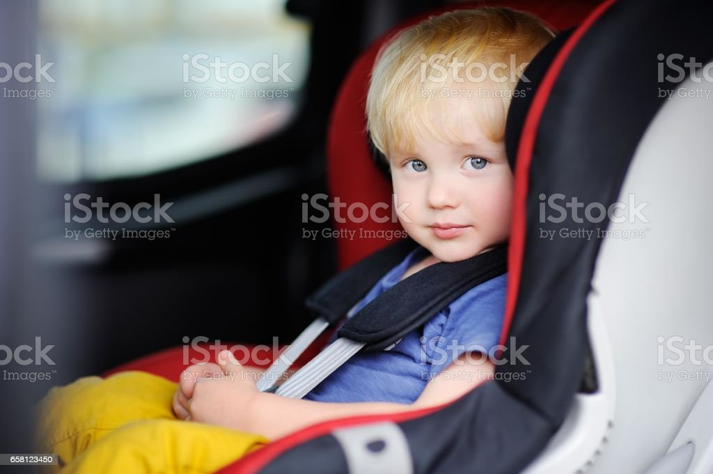 Portrait of cute toddler boy sitting in car seat royalty-free stock photo