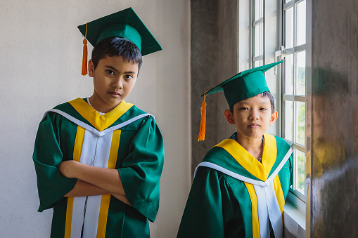 Portrait of cute two Asian boys wearing graduation hat and gowns standing in classroom at school, Elementary School and students concept