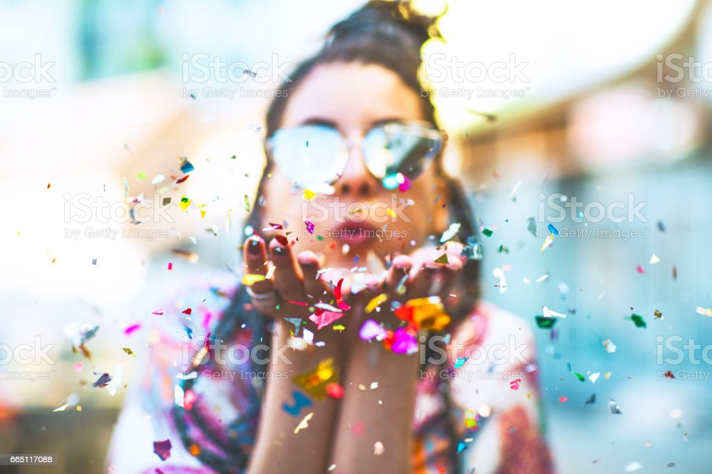 Portrait of cute woman blowing confetti stock photo
