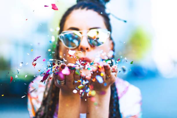 Portrait d'une femme mignonne soufflant confetti - Photo