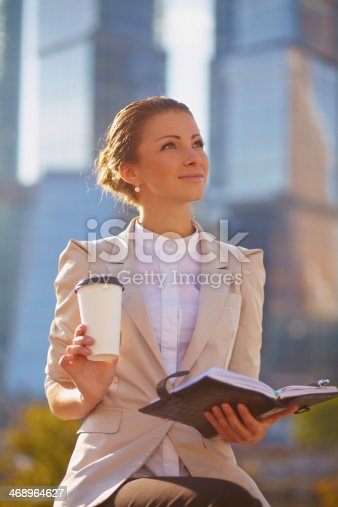 istock Portrait of cute young business woman outdoor with notebook 468964627