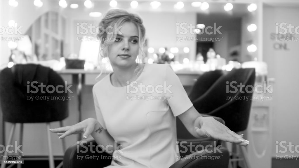 portrait of cute young girl sit in armchair in makeup room black and