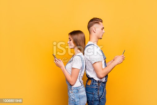 Portrait of cute young students couple wearing casual, standing back to back, holding their smartphones in hands, seriously looking at screens, over yellow background, isolated, copyspace