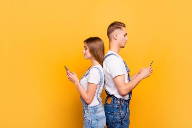 porträt von niedlichen jungen studenten paar tragen lässig, rücken an rücken stehend, ihre smartphones in den händen halten, ernsthaft auf der suche an den bildschirmen, auf gelbem hintergrund, isoliert, exemplar - jeans overall stock-fotos und bilder