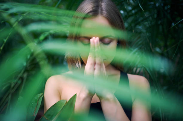 Portrait of cute young woman meditating and doing namaste hand in jungle. Sunny day stock photo