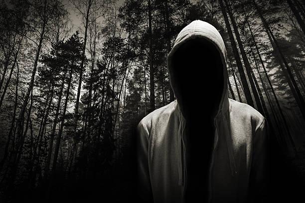 Retrato de homem perigoso sob o capô na floresta - foto de acervo
