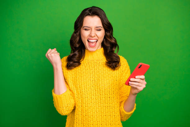 Portrait of delighted energetic girl use smartphone achieve hundred followers on social media raise fists scream yes wear winter style sweater isolated over bright shine color background stock photo