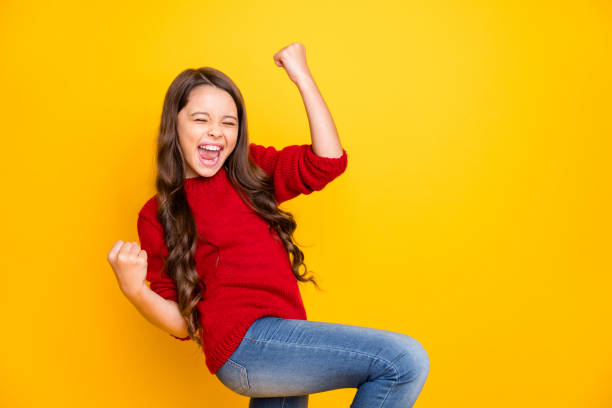 Portrait of delighted positive lucky cheerful kid feel crazy funky rejoice raise fists scream yeah celebrate achievements aims wear style sweater denim jeans isolated over yellow color background stock photo