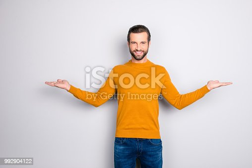 istock Portrait of delightful confident expert attractive bearded guy demonstrating balance  giving two options wearing mustard color sweater jeans isolated on gray background copyspace 992904122