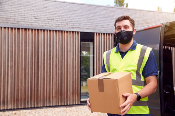 Portrait Of Delivery Driver Wearing Mask Holding Package Outside House stock photo