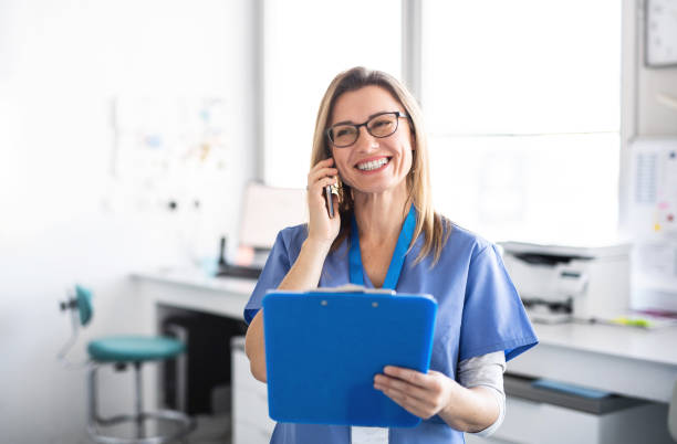 Ein Porträt der Zahnarzthelferin in der modernen Zahnchirurgie, mit dem Smartphone. – Foto