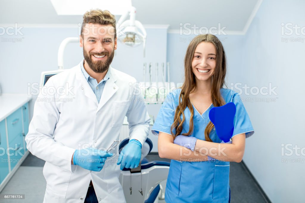 Portrait of handsome dentist with young female assistant in uniform...