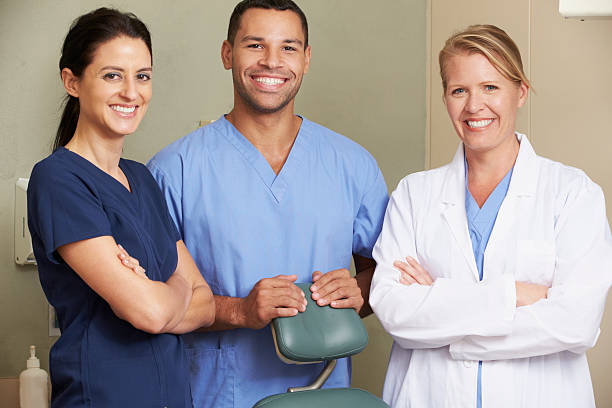 portrait of dentist and dental nurses in surgery - three people stock photos and pictures