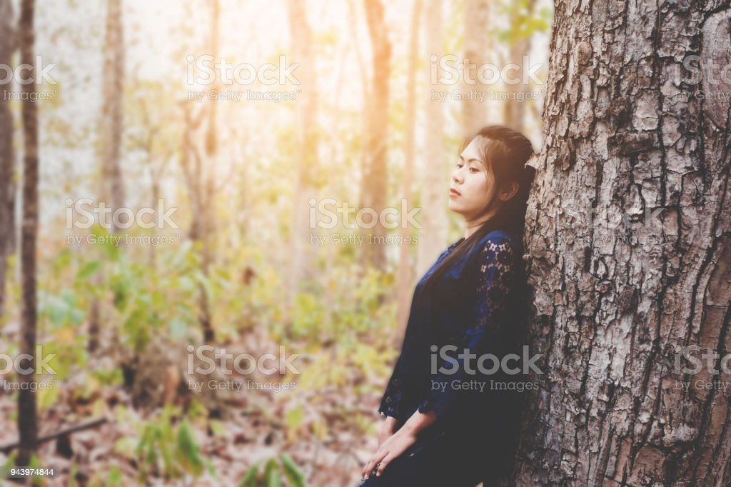 portrait of depress and hopeless young woman calm herself in forest at countryside stock photo