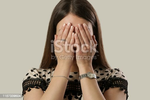 932187866istockphoto Portrait of depressed woman, covering face with her hands 1157339504