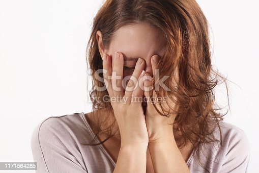 932187866istockphoto Portrait of depressed woman, covering face with her hands 1171564285