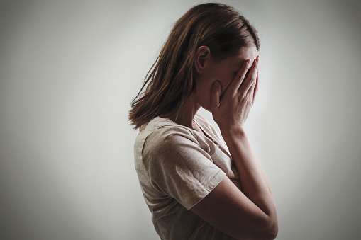 Portrait Of Depressed Woman Covering Face With Her Hands Side View Stock Photo - Download Image Now