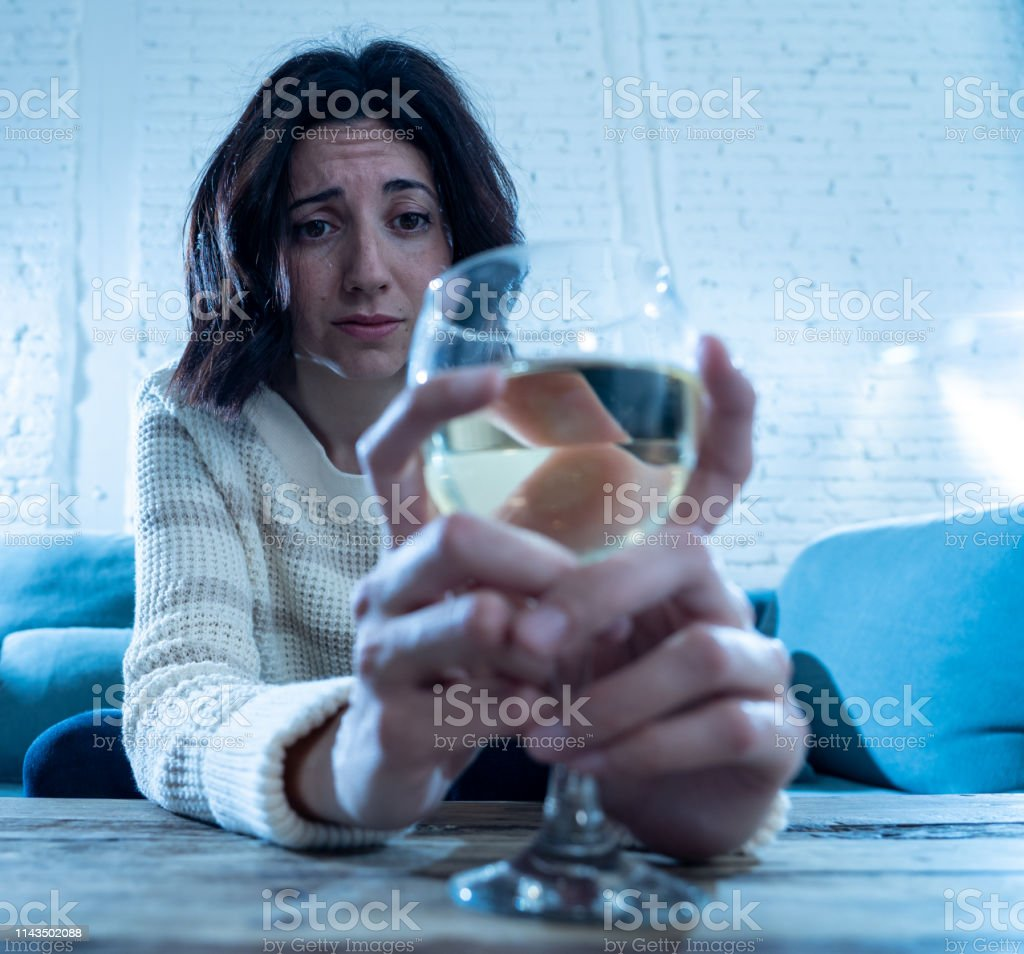 Portrait of depressed woman drinking glass of wine alone at home....