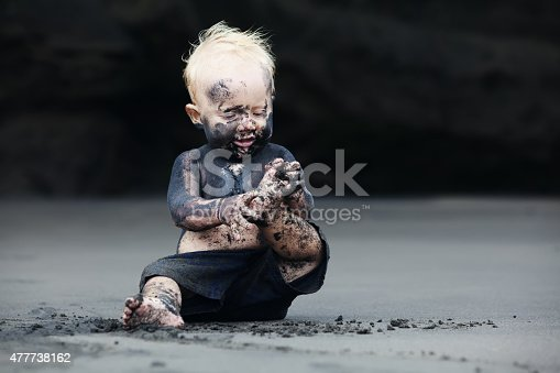istock Portrait of dirty child on the black san beach 477738162