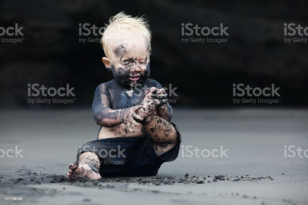 Portrait of dirty child on the black san beach stock photo