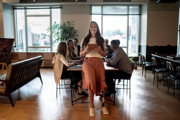 会議テーブルでデジタルタブレットを使用して障害のある切断者リーダービジネスウーマンの肖像画 - disabilitycollection ストックフォトと画像