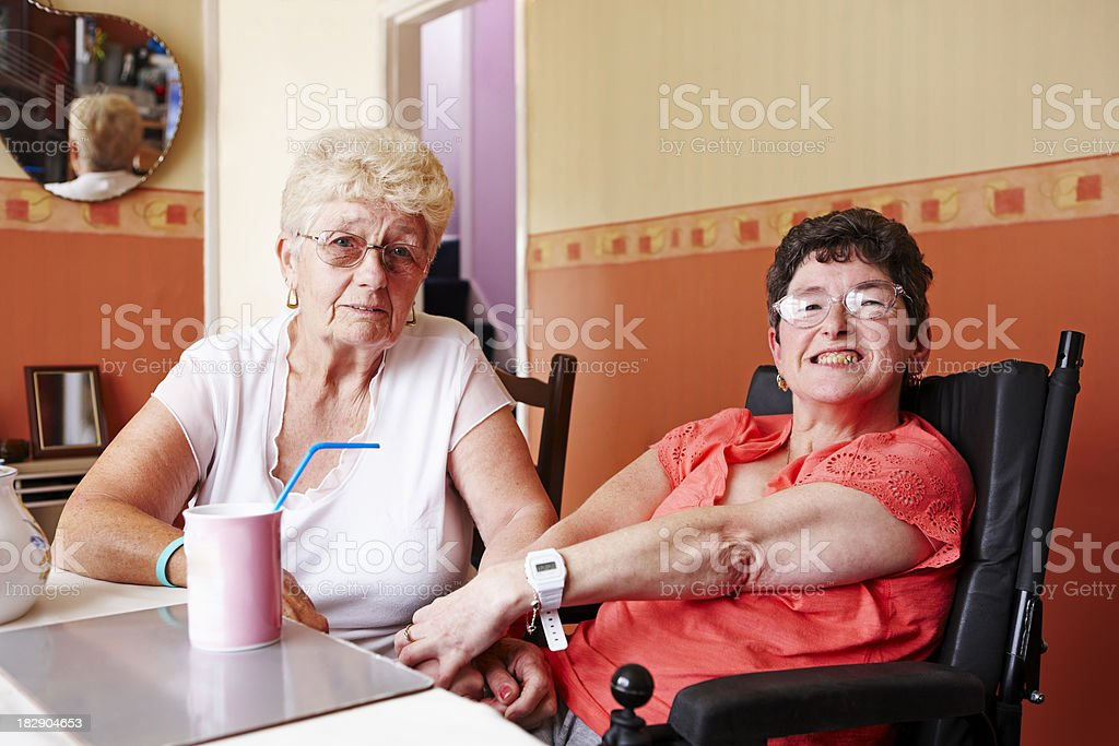 portrait of disabled woman with her mother at home stock photo