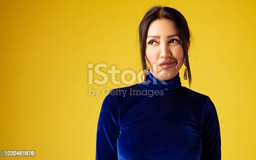 Woman looking disappointed front of yellow background.