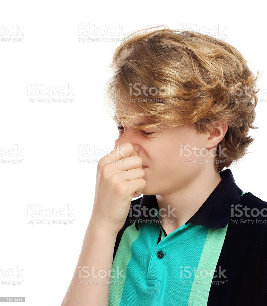 Portrait of disgusted teenage boy pinches her nose royalty-free stock photo
