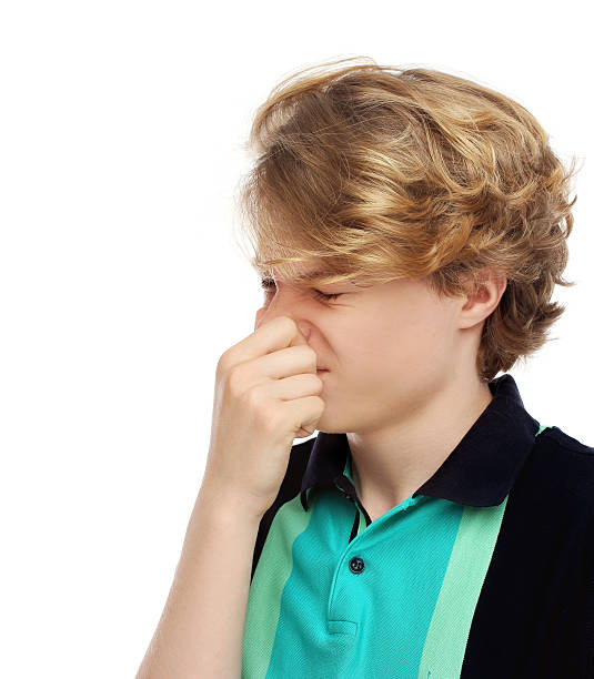 Portrait of disgusted teenage boy pinches her nose stock photo