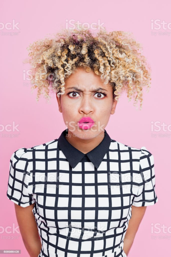 Portrait of displeased afro american young woman Studio portrait of disgusted afro american young woman staring at the camera. Pink background. 20-24 Years Stock Photo