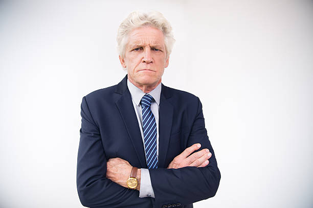 portrait of displeased senior businessman in suit - frowning stock photos and pictures