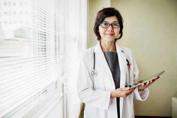 portrait du docteur holding presse-papiers - une seule femme senior photos et images de collection