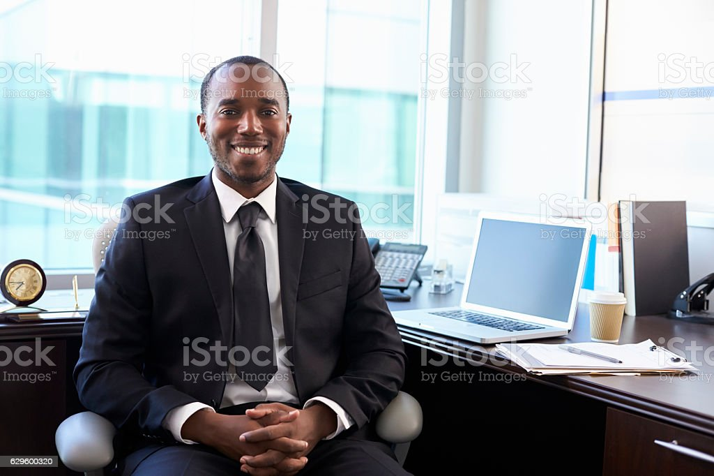 Portrait Of Doctor Sitting At Desk In Office stock photo