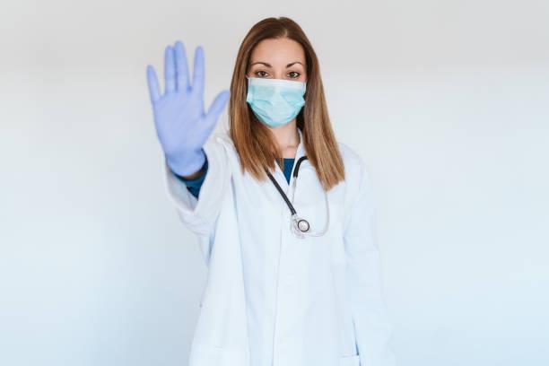 retrato de la doctora mujer usando máscara protectora y guantes en interiores. Haciendo una señal de alto con la mano. Concepto de virus corona - foto de stock