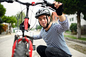 istock Portrait of down syndrome adult man with bicycle standing outdoors on street. 1289758903