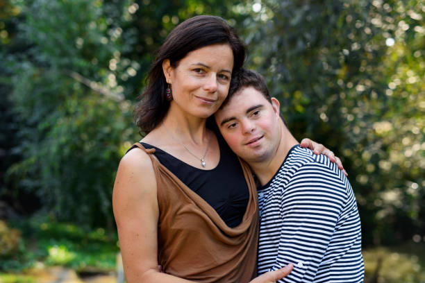 Portrait of down syndrome adult man with mother standing outdoors in garden. stock photo