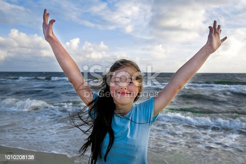 istock Portrait of down syndrome girl smiling on background of the sea 1010208138