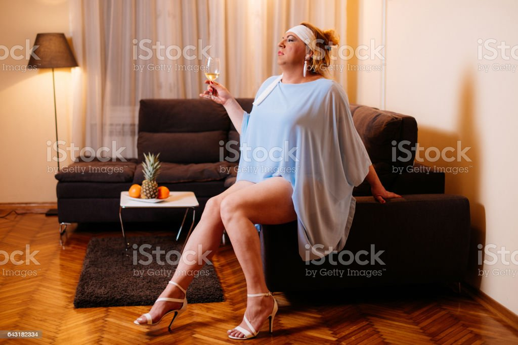 Portrait of drag queen in light blue dress and high heels - transsexual person at home stock photo