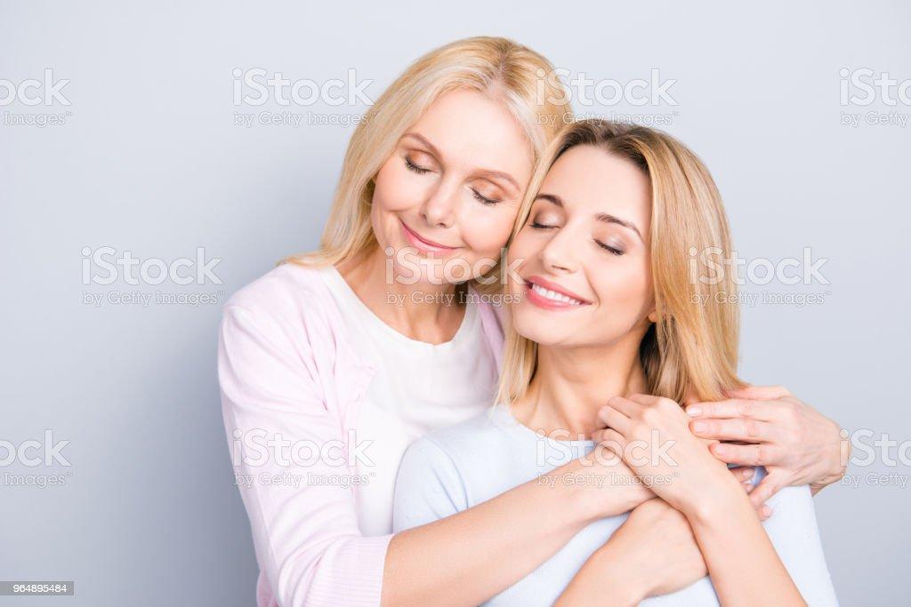 夢幻般可愛可愛的媽媽和成人的孩子的肖像, 溫暖的擁抱, 保持眼睛緊閉, 穿著休閒裝享受時間在一起孤立的灰色背景 - 免版稅一起圖庫照片