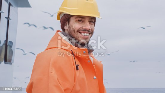 Portrait of Dressed in Bright Protective Coat Smiling Fisherman on Commercial Fishing Boat.