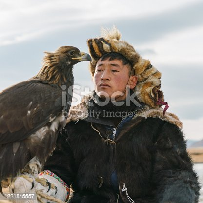 Portrait of eagle hunter  near the river  in Mongolia