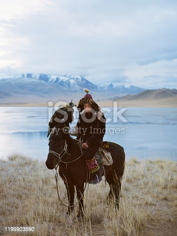 Portrait of eagle hunter on horse in desert in Mongolia