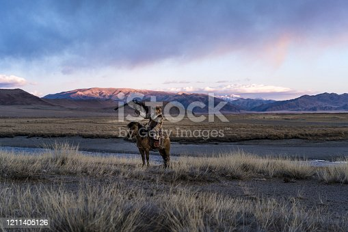 Portrait of eagle hunter on horse in steppe  in Mongolia