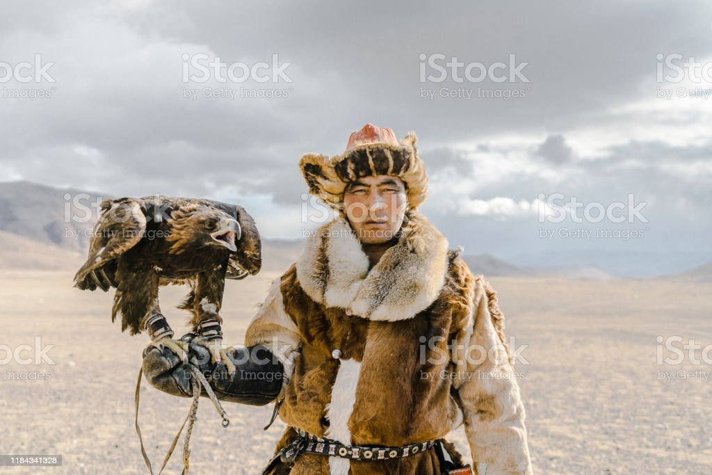 Portrait of eagle hunter standing in desert in Mongolia Portrait of eagle hunter standing in desert in Mongolia Adult Stock Photo