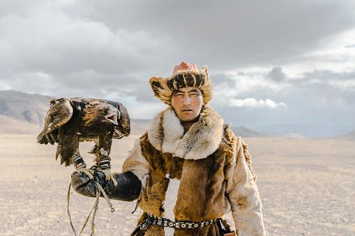 Portrait of eagle hunter standing in desert in Mongolia
