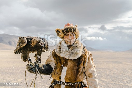 Portrait of eagle hunter standing in desert in Mongolia