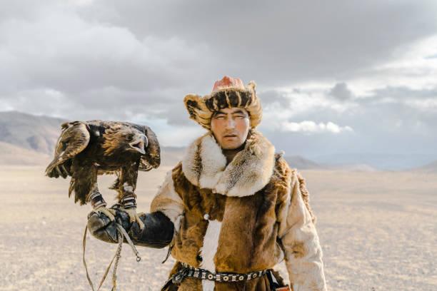 Portrait of eagle hunter standing in desert in Mongolia stock photo