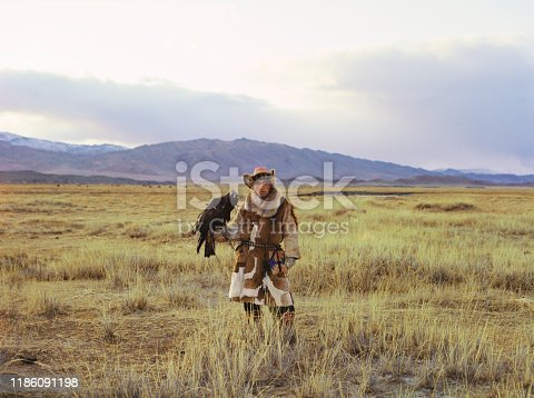 istock Portrait of eagle hunter standing in steppe in Mongolia 1186091198